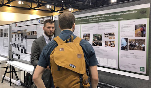 Sebastian Barkett talks with a conference goer in front of his research poster
