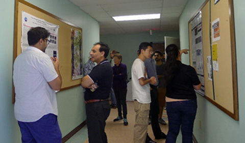 Several PBIO students discussing their research with PBIO Faculty and other PBIO students during graduate symposium