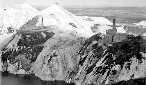 a black and white aerial photo of two engine houses on the edge of a cliff