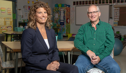 Dr. Julie Owens and Dr. Steve Evans, sitting in a school classroom