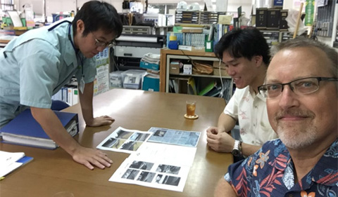 Viewing documents related to the lost-then-found fishing vessel from Iwate: Masaru Yonashiro of the Kinjo-cho town hall, Koudai Nakada and Chris Thompson
