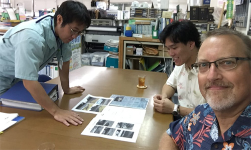 Masaru Yonashiro of the Kinjo-cho Town Hall, Nakada, and Thompson viewing documents related to the fishing vessel from Iwate.