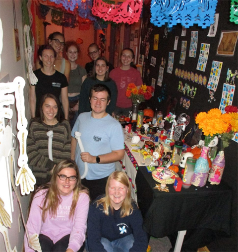 Members of Sigma Delta Pi and the Spanish Club pose with their altar after decorating Gordy Hall for Día de los Muertos.