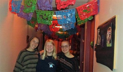 Three of Sigma Delta Pi's members pose under papel picado while decorating Gordy Hall for Día de los Muertos.