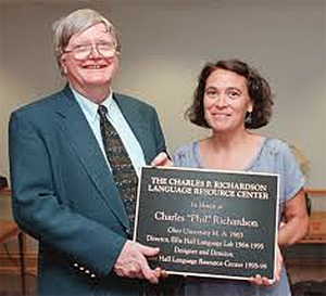 "Phil Richard holding plaque naming ""The Charles P. Richardson Language Resource Center."""