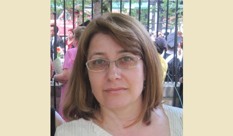 A woman with short brown hair and glasses
