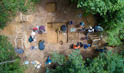 Overhead shot: Students and community members excavate a site in the Wayne National Forest as part of the Archaeology field school.