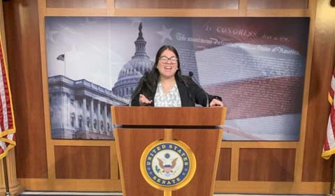 Esther Aulis-Cabrera strikes a pose at a U.S. Senate podium.