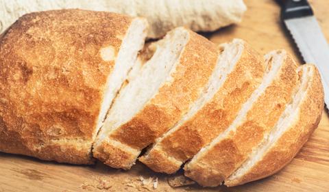 Ciabatta bread loaf slices on wooden board with knife. Fresh crusty white wheat bread Italian cuisine