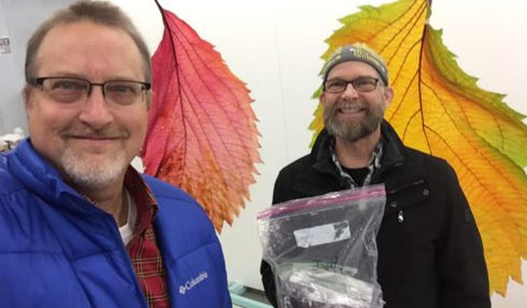 John Sabraw, right, is holding plastic bags containing dirt from Iwate and Aichi brought back by Chris Thompson to make into paint for the mural project. This photo was taken in December 2019.