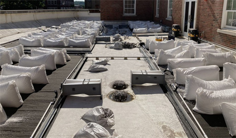 The beds are fitted with the flumes that will allow us to measure water flow from the beds before they enter the drains. The drainage fabric is held down overnight with bags of lightweight growing media.