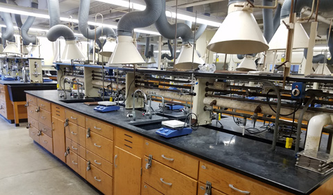 The old chemistry lab in the basement of Clippinger Laboratory, with dark and dreary furniture and ventilation system.