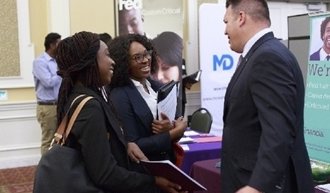 Photo of students talking to recruiter at career fair.