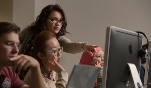 Gabriela Castañeda-Gleason working with students at a computer