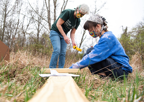 Dr. Kim Thompson and Mikayla Schuyler screw bat houses to a post.