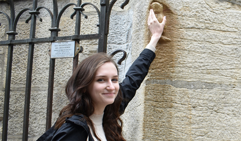 Leah Allan touching the owl carved into the Notre Dame de Dijon (a good luck symbol) on the Global Consulting Program (GCP) trip to Dijon France, March 11, 2019.